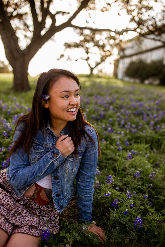 Female college graduate sitting in bluebonnet field at St. Edward's University. Photo by Erin Reas senior photographer in Austin, Texas