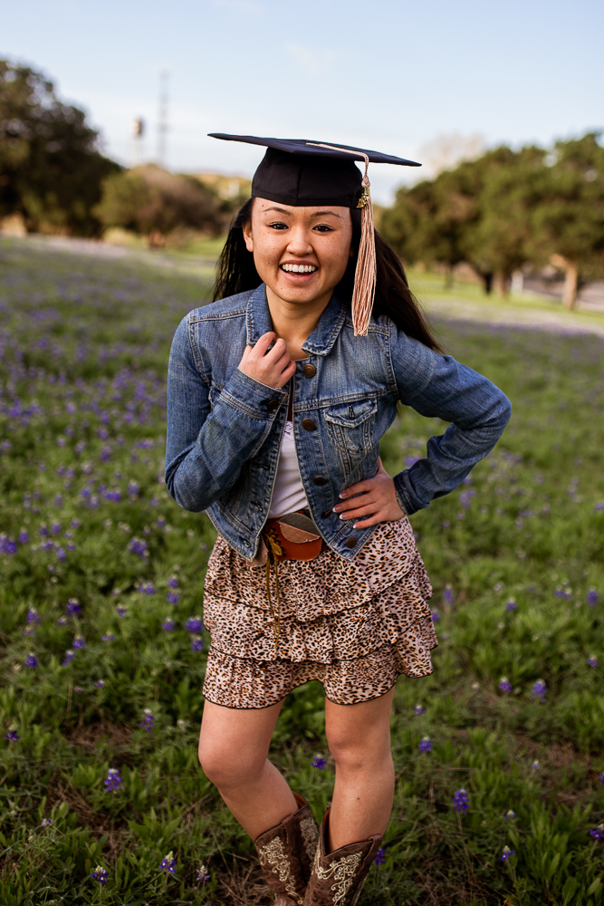 Female Asian college graduate wearing cowboy boots and jean jacket. Senior portrait in a bluebonnet field. Photo by senior photographer Erin Reas in Austin, Texas.