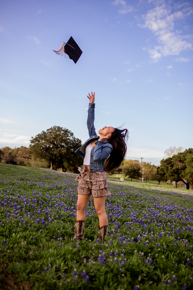 Female college graduate tossing grad cap into the air standing in a field of bluebonnets at St. Edward's University. Photo by Erin Reas local Austin, Texas senior photographer