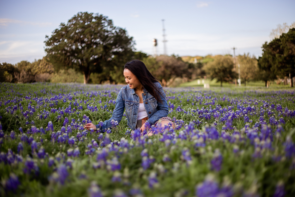 Young adult woman sitting among a field of bluebonnets in Austin, Texas. Lifestyle portrait photography by Erin Reas.