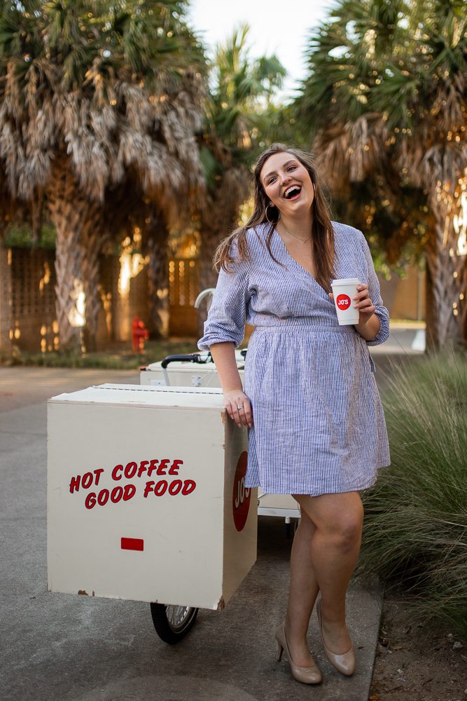 College senior at St. Edward's University holding Jo's coffee cup and standing next to coffee cart. Photo by Erin Reas senior photographer in Austin, TX