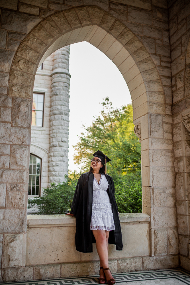 Female college graduate wearing cap and gown at St. Edward's University. Photo by Erin Reas senior photographer in Austin, Texas