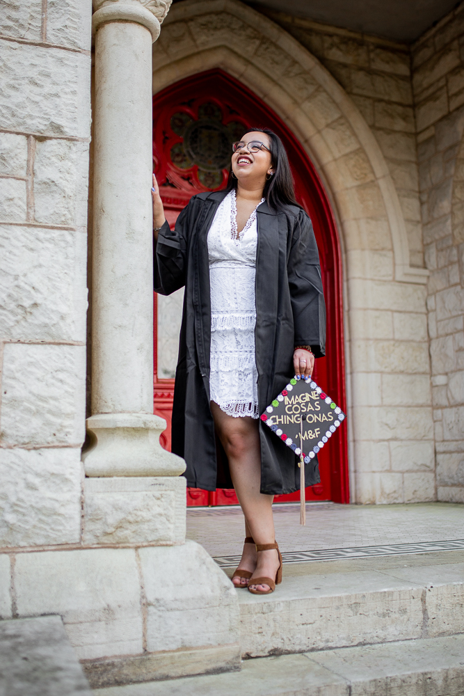 Female Latina college graduate holding decorated cap. Photo by Erin Reas senior photographer in Austin, TX