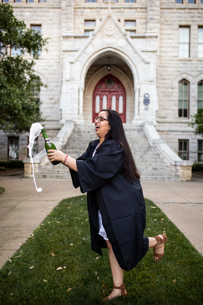 Female college graduate popping champagne during grad shoot at St. Edward's University in front of Main Building. Photo by Erin Reas senior photographer in Austin, TX