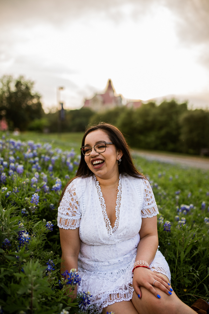 Female college graduate at St. Edward's University sitting in field of bluebonnets. Photo by Erin Reas Austin, TX senior photographer