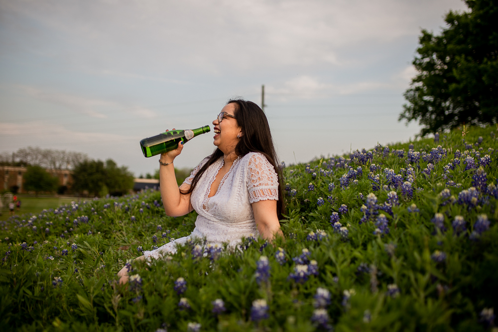 Female college graduate sitting in a field of bluebonnets at St. Edward's University while drinking a bottle of champagne. Photo by Erin Reas senior photographer in Austin, TX