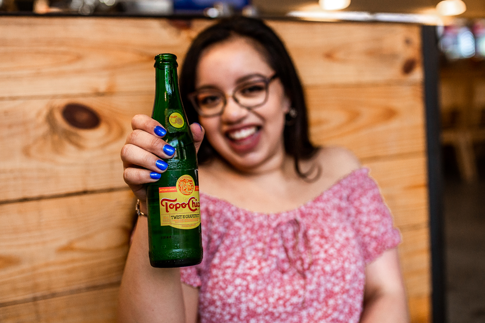 College graduate drinking Topo Chico during senior portrait session at St. Edward's University. Photo by Erin Reas senior photographer in Austin, TX