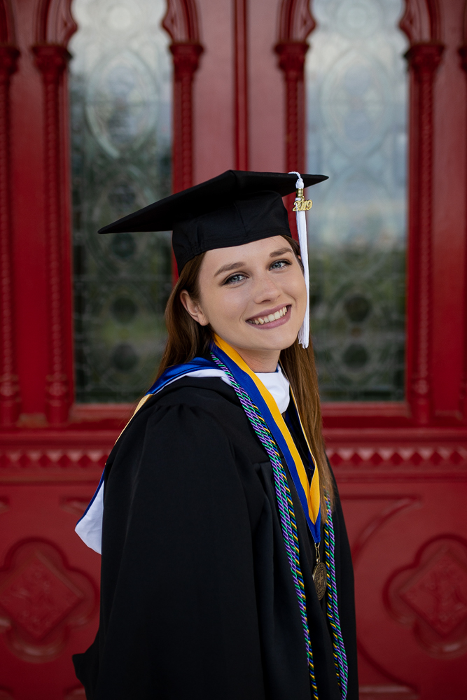 Female college graduate in cap and gown standing in front of Red Doors at St. Edward's University. Photo by Erin Reas local senior photographer in Austin, Texas