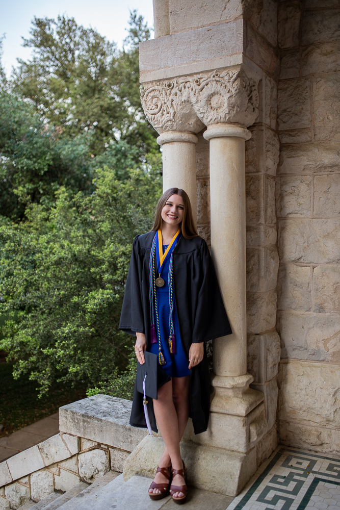 Female college graduate wearing cap and gown standing at the top of St. Edward's University Main Building in Austin, Texas. Photo by Erin Reas senior photographer