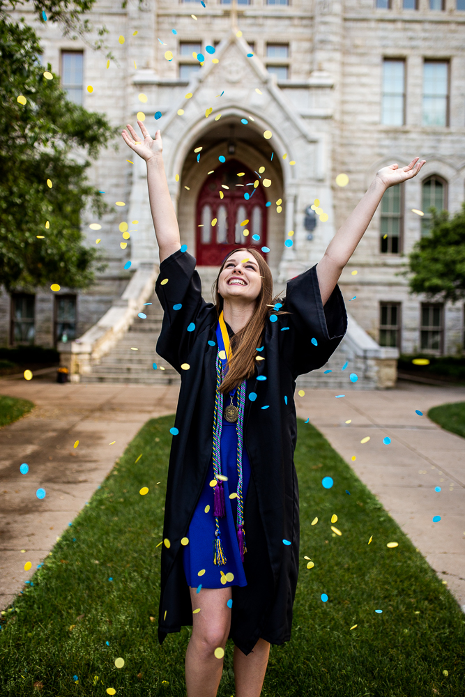Female college graduate throwing blue and yellow confetti in front of Main Building at St. Edward's University. Photo by Erin Reas senior photographer in Austin, Texas