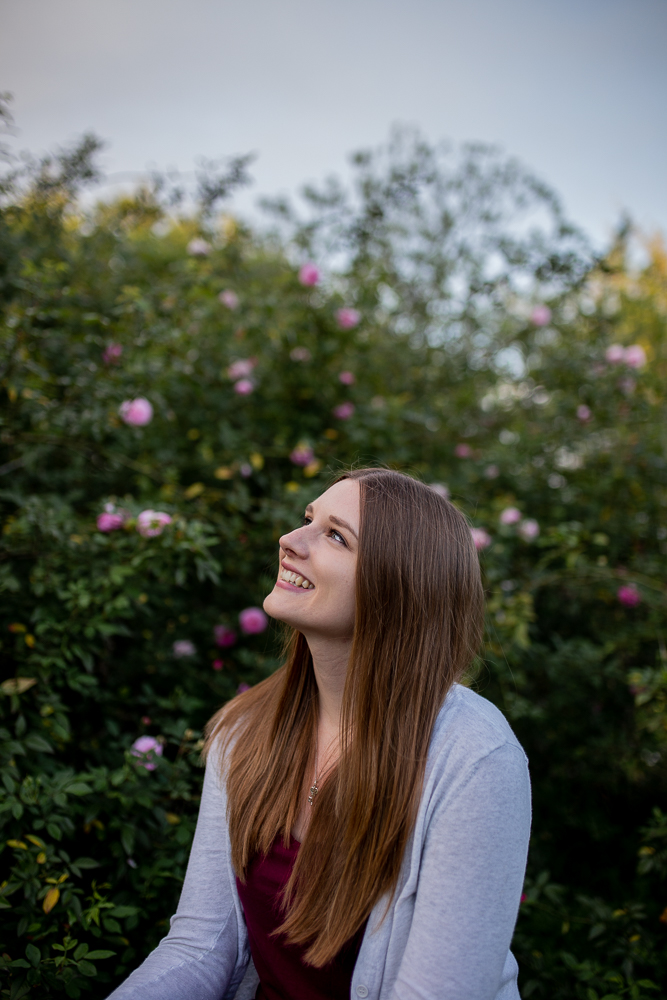 female college senior wearing a cardigan and maroon top sitting in front of rose bushes at St. Edward's University. Photo by Erin Reas Austin, TX senior photographer
