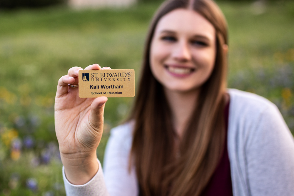 college graduate with degree in teaching at St. Edward's University holding name tag. Photo by Erin Reas Austin, TX senior photographer