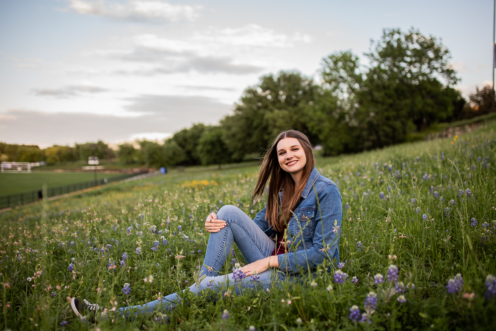 Female college senior sitting in field of wildflowers with leg bent and wearing blue jean jacket. Photo by Erin Reas senior photographer in Austin, TX