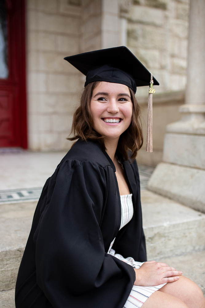 Female college graduate wearing cap and gown sitting on steps of Main Building at St. Edward's University. Photo by Erin Reas senior photographer in Austin, TX