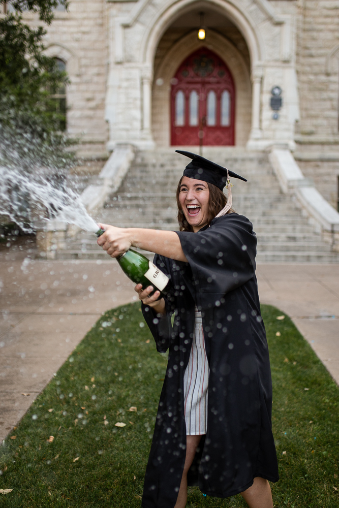 College senior popping bottle of champagne and spraying it at St. Edward's University. Photo by Erin Reas senior photographer in Austin, TX.