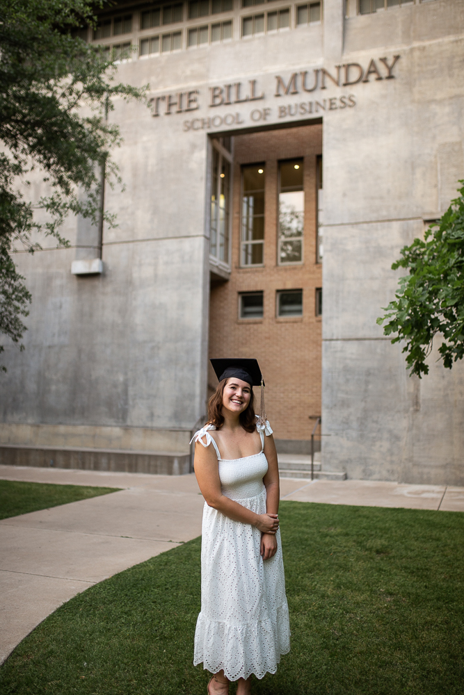 Female college graduate wearing white dress standing in front of Trustee Hall at St. Edward's University. Photo by Erin Reas senior photographer in Austin, TX