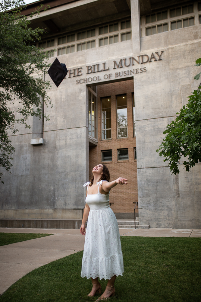 Female college graduate wearing white dress and tossing graduation cap in the air. Photo by Erin Reas senior photographer in Austin, TX