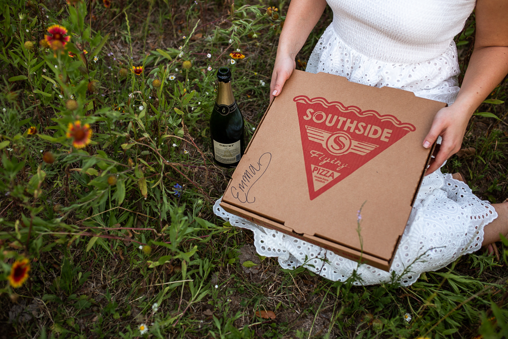 Southside Flying Pizza pizza box with bottle of champagne. Photo by Erin Reas senior photographer in Austin, TX