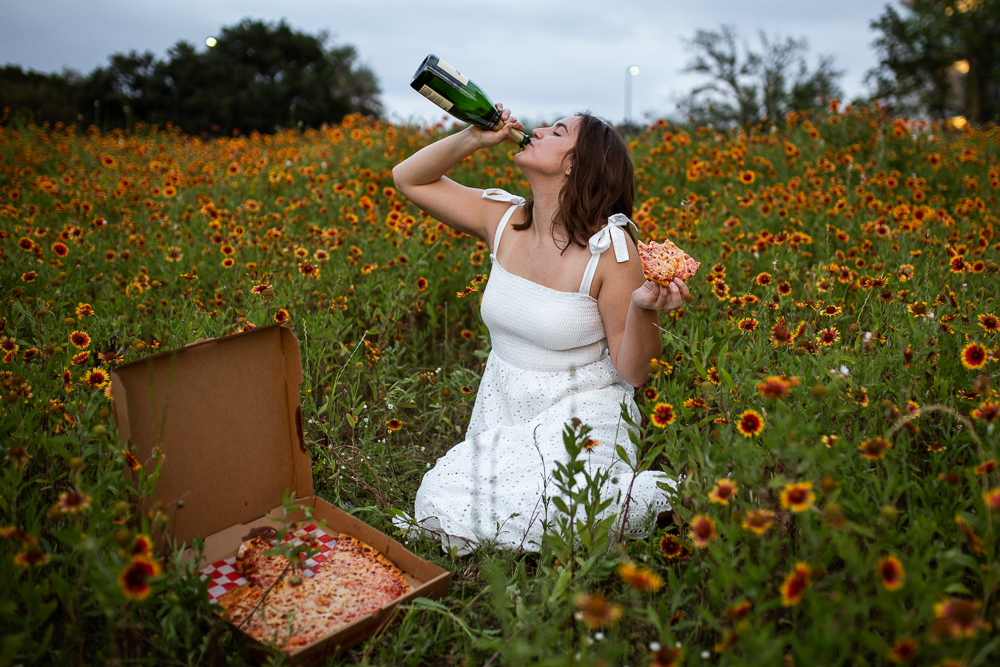 College graduate at St. Edward's University eating pizza and drinking a bottle of champagne in a field of Indian Paintbrushes. Photo by Erin Reas senior photographer in Austin, TX. Pizza from Southside Flying Pizza