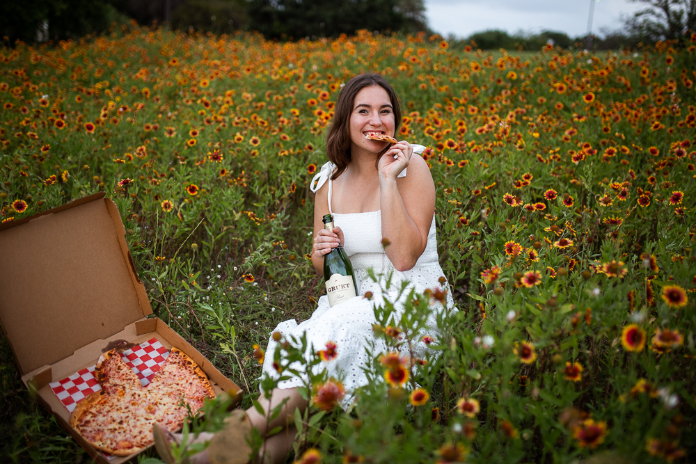 College graduate at St. Edward's University eating pizza in a field of Indian Paintbrushes. Photo by Erin Reas senior photographer in Austin, TX. Pizza from Southside Flying Pizza