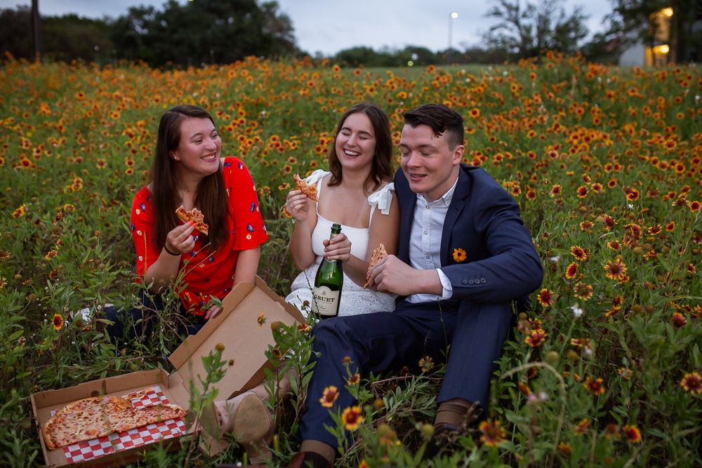 Group of college friends eating pizza and drinking champagne in a field of Indian Paintbrushes at St. Edward's University. Photo by Erin Reas senior photographer in Austin, TX