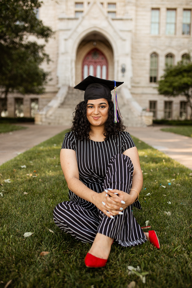 Female college graduate sitting on Main Lawn of St. Edward's University wearing red heels and cap. Photo by Erin Reas senior photographer in Austin, TX