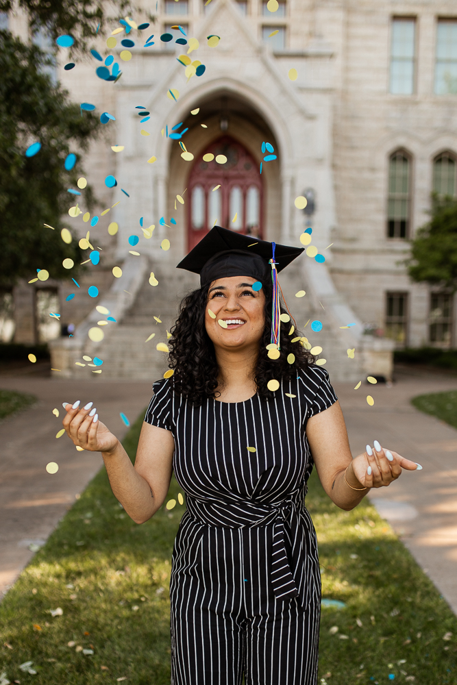 Female college graduate wearing striped jumpsuit and grad cap throws blue and yellow confetti in the air at St. Edward's University. Photo by Erin Reas senior photographer in Austin, TX