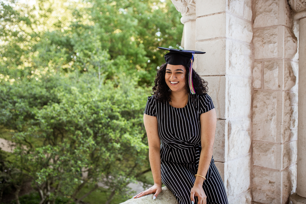 Female college senior wearing grad cap and sitting on ledge of building. Photo by Erin Reas senior photographer in Austin, TX