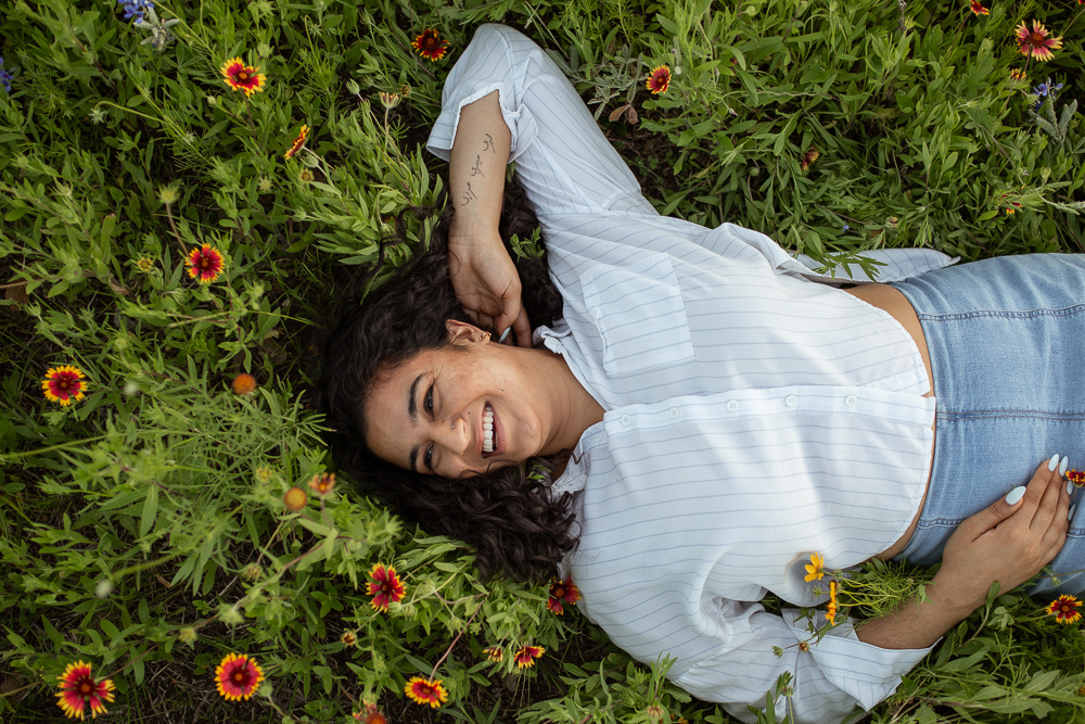 Female college senior laying down in a field of wildflowers. Photo by Erin Reas senior photographer in Austin, TX