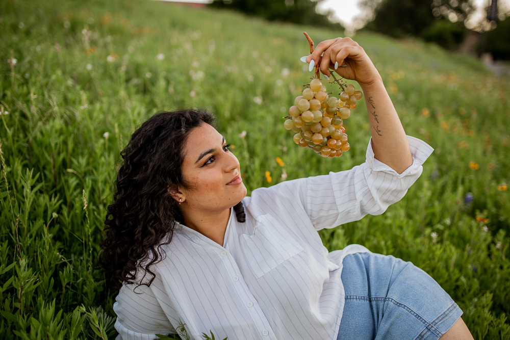 Female college senior laying in a field of flowers with a bundle of grapes. Photo by Erin Reas senior photographer in Austin, TX
