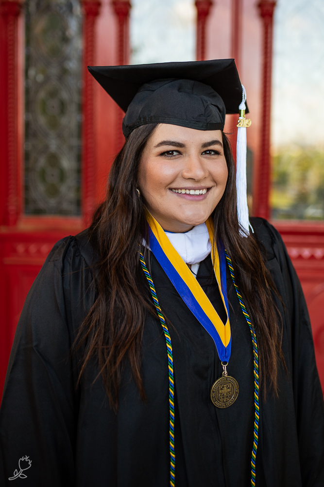 Female college graduate wearing cap and gown standing in front of red doors at St. Edward's University.