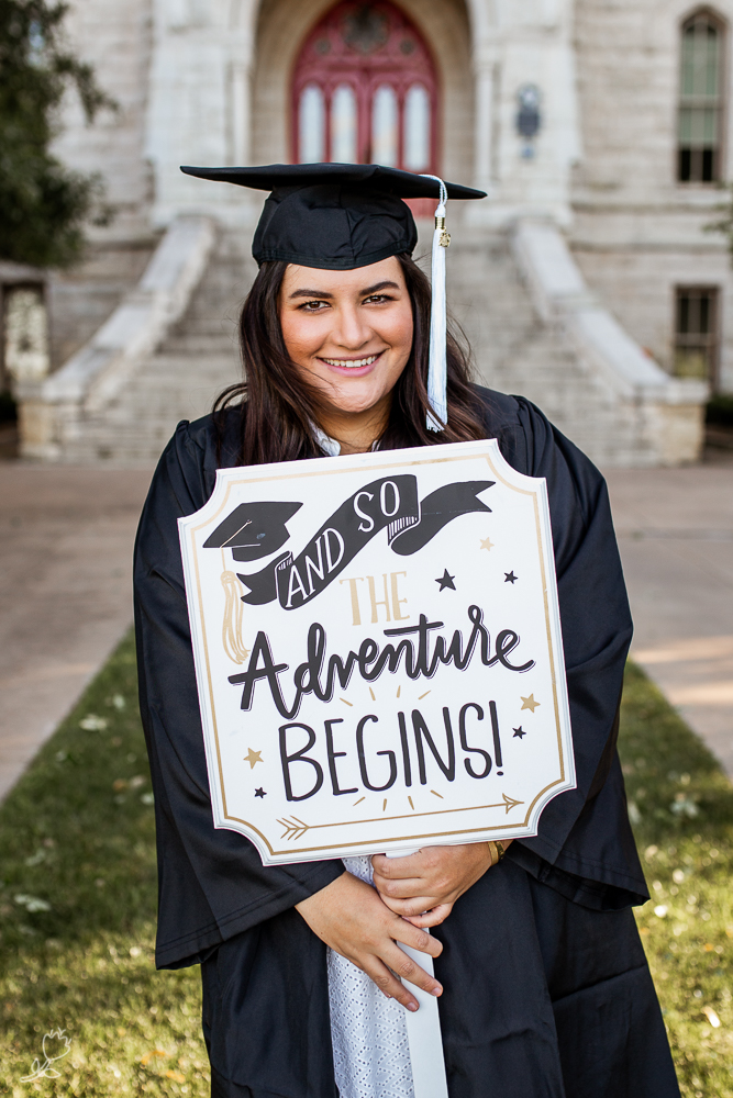 Female college graduate at St. Edward's University holding graduation sign in front of Main Building. Photo by Erin Reas Austin senior photographer.