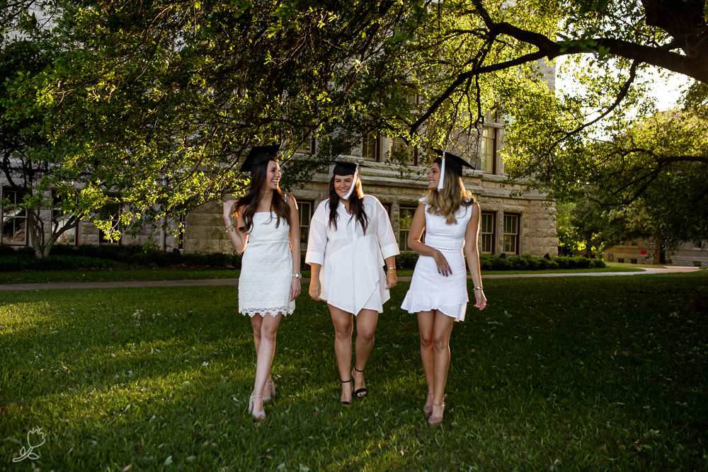 College graduates best friends wearing white dresses and graduation caps looking at each other and laughing. Photo taken at St. Edward's University by Erin Reas a senior photographer.