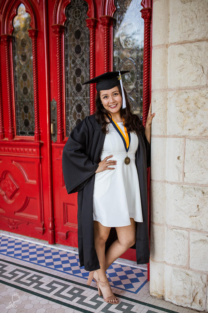 Female college graduate standing in front of red doors at St. Edward's University. Photo by Erin Reas senior photographer in Austin, TX