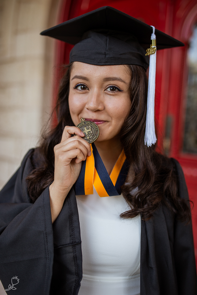Female college graduate standing in front of red doors at St. Edward's University kissing school medallion. Photo by Erin Reas senior photographer in Austin, TX