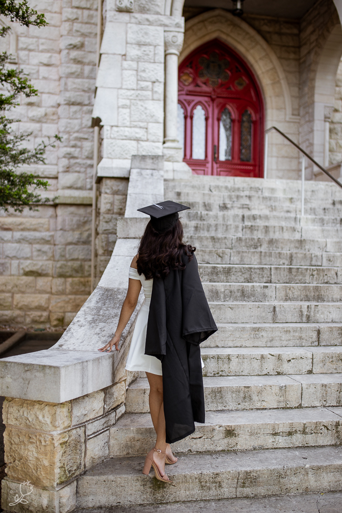 Female college graduate standing at base of Main Building at St. Edward's University walking up steps while wearing cap and gown over a white dress. Photo by Erin Reas senior photographer