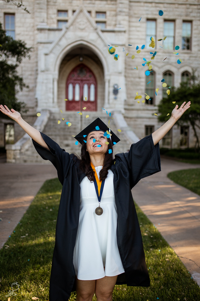 St. Edward's University college graduate throwing blue and yellow confetti in front of Main Building. Photo by Erin Reas senior photographer in Austin, TX