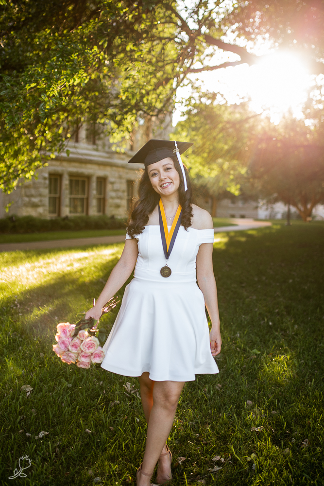 Senior girl wearing white dress and standing in hazy golden hour light at St. Edward's University. Photo by Erin Reas senior photographer in Austin, TX
