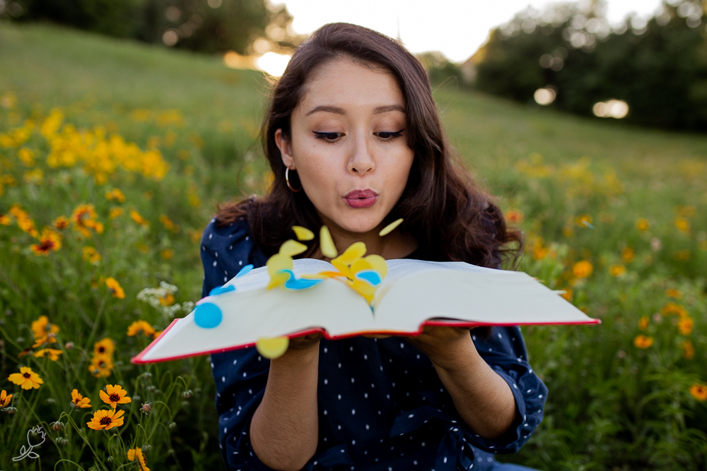Lifestyle photo of girl blowing confetti out of book. Photo by Erin Reas senior photographer in Austin, TX
