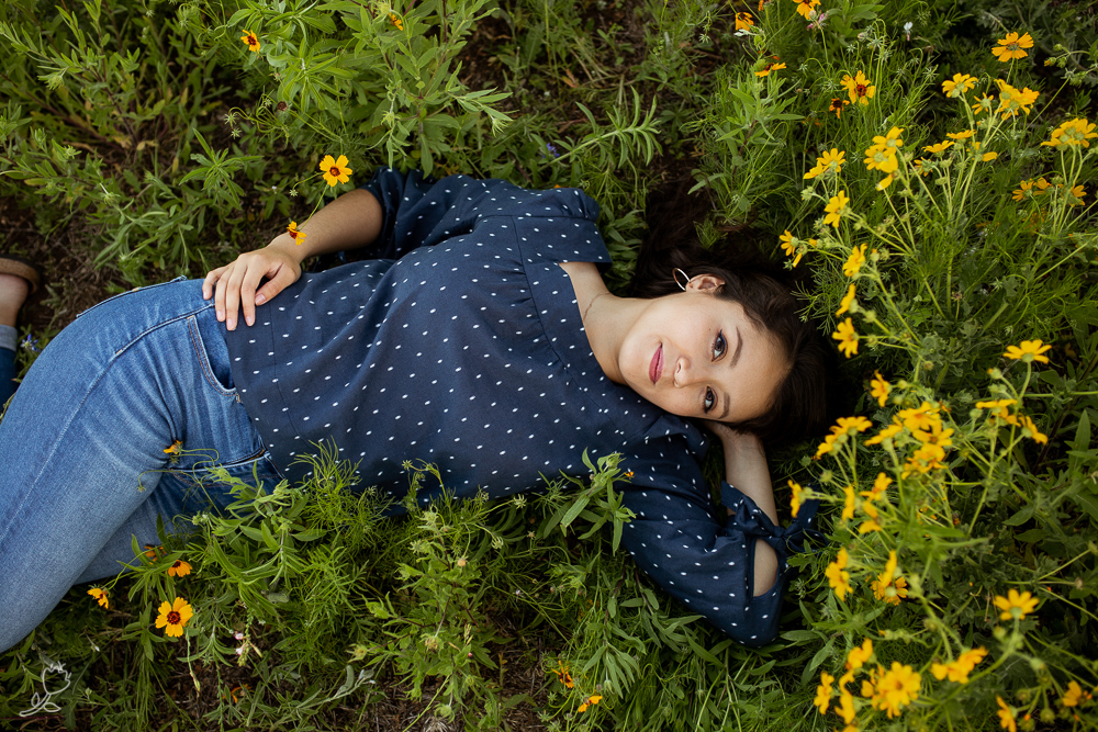 Aerial view of senior girl lying in a field of flowers. Photo by Erin Reas senior photographer in Austin, TX