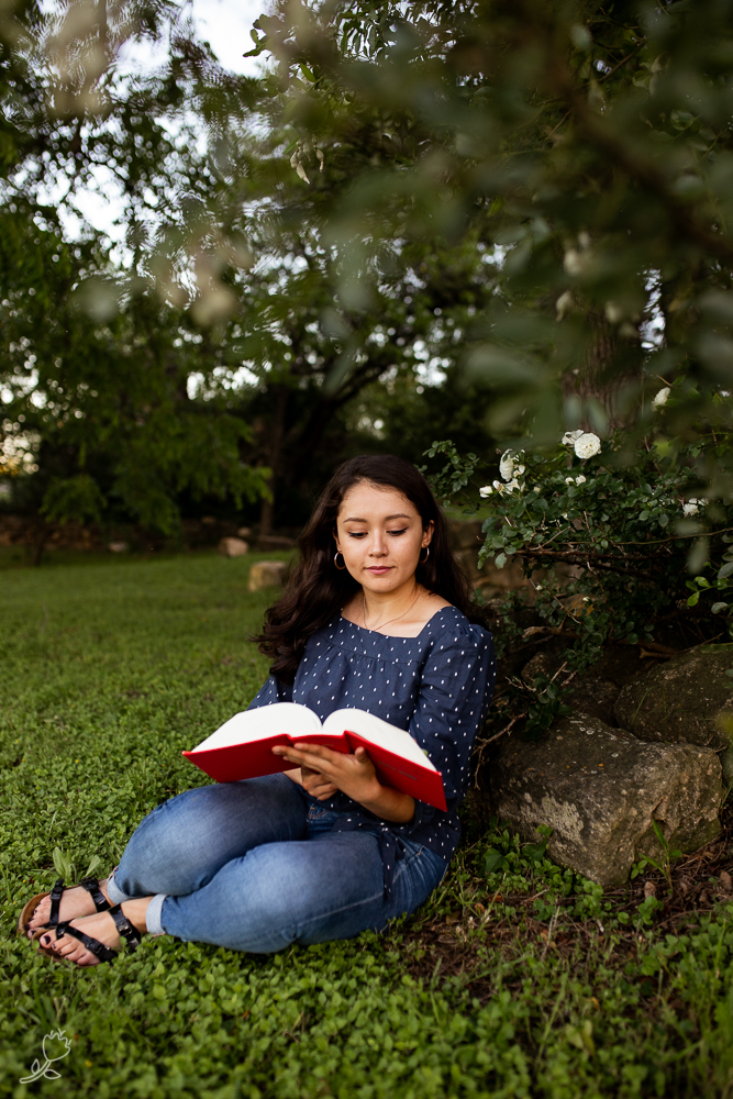Female college senior sitting underneath tree and reading a book. Photo by Erin Reas senior photographer in Austin, TX