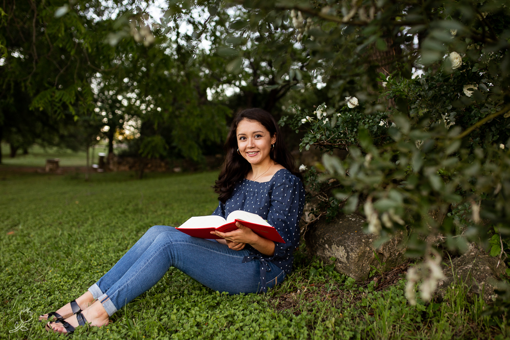 Female senior sitting with a book in her lap underneath a tree at St. Edward's University. Photo by Erin Reas senior photographer in Austin, TX