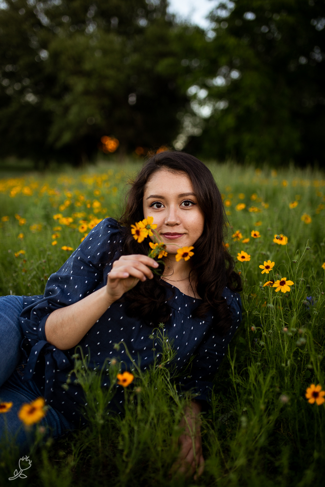Senior lifestyle portrait sitting in a field of flowers. Photo by Erin Reas college senior photographer in Austin, TX