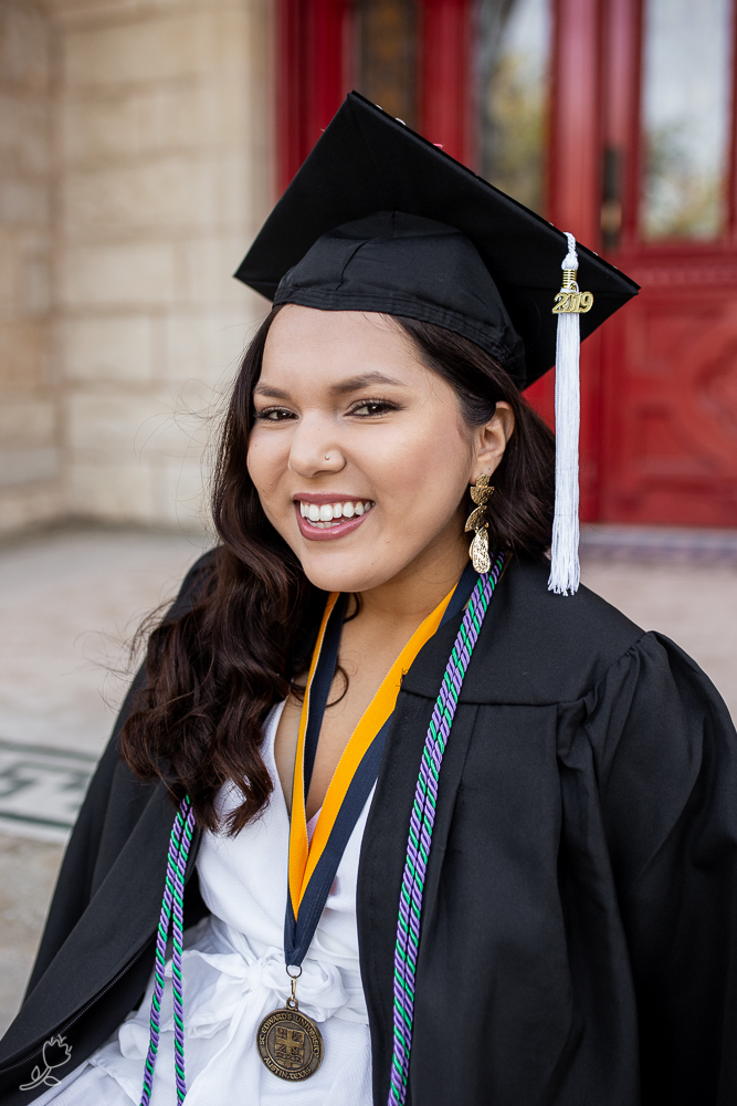 Female college graduate standing in front of red doors at St. Edward's University while wearing cap and gown. Photo by Erin Reas Austin, TX senior and lifestyle photographer.