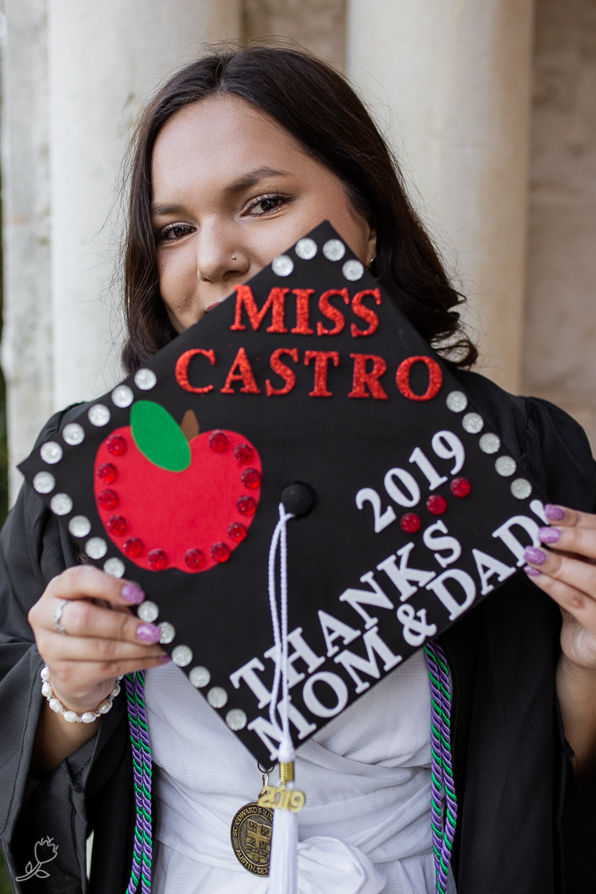 College graduate holding decorated graduation cap. Graduate with a teaching degree at St. Edward's University. Photo by Erin Reas senior photographer in Austin, Texas