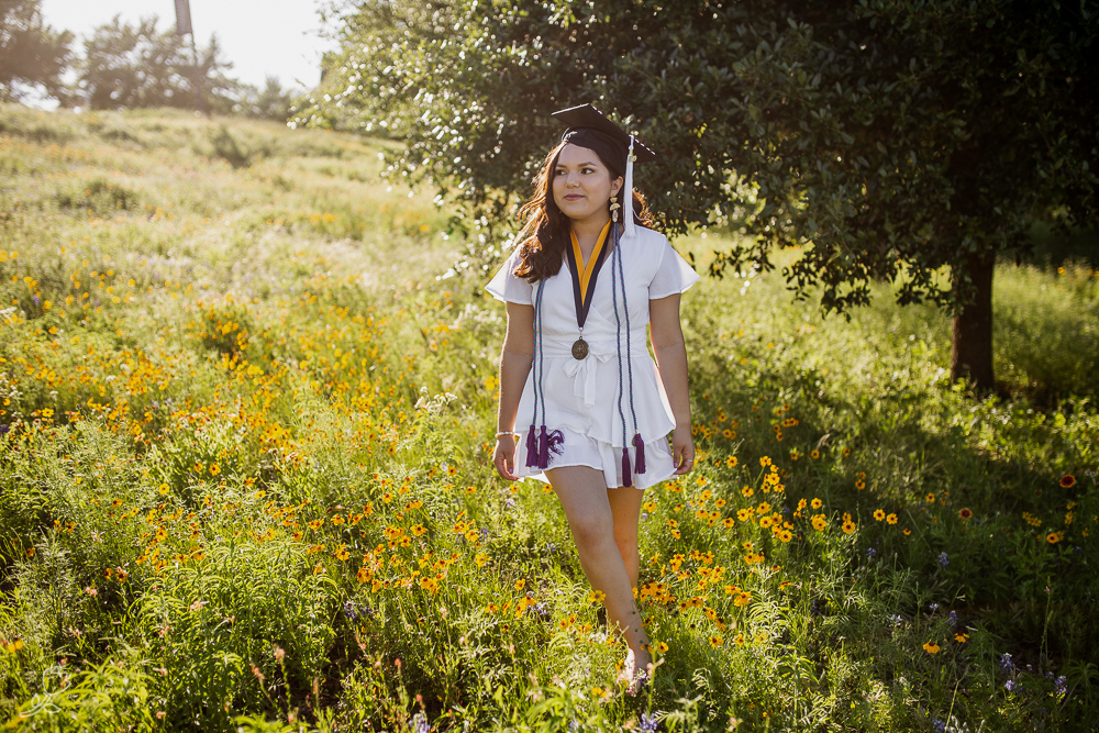 Female college graduate wearing white dress walking in a field of wildflowers during golden hour. Photo by Erin Reas senior photographer in Austin, TX
