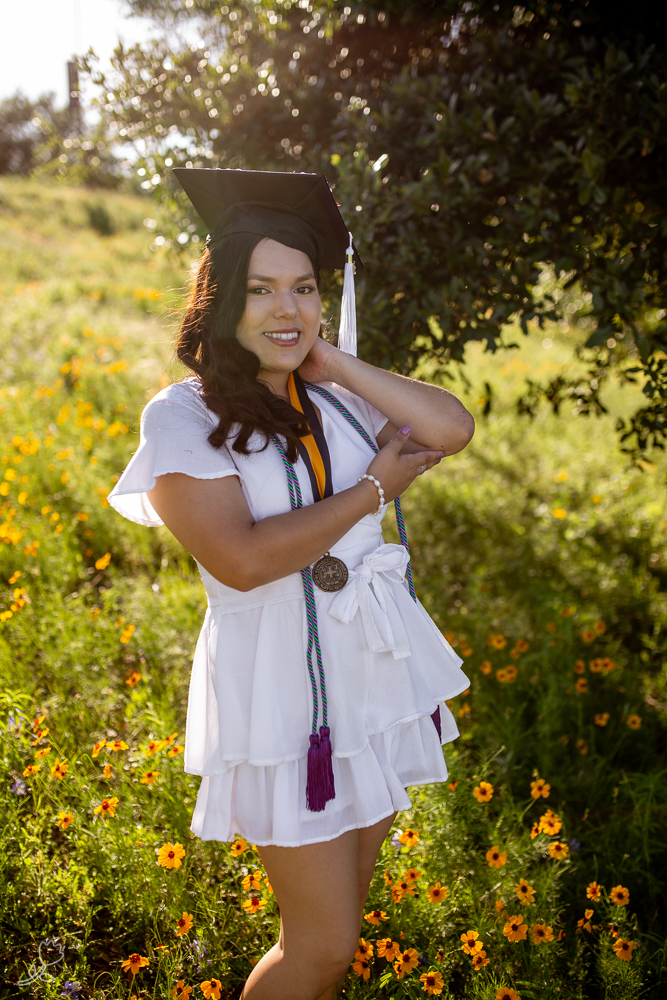 Female college graduate standing in a field of wildflowers during golden our. Photo by Erin Reas senior photographer in Austin, TX