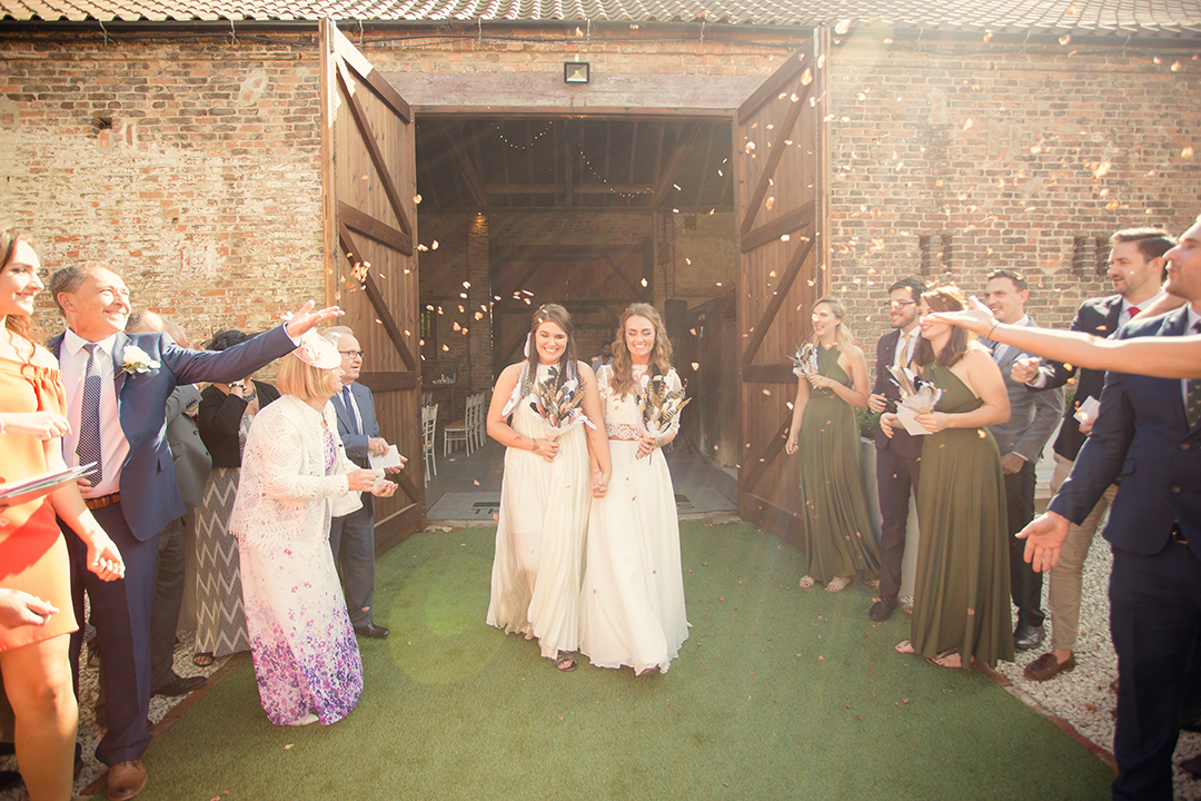 The brides are greeted by guests after their beautiful ceremony at The Normans