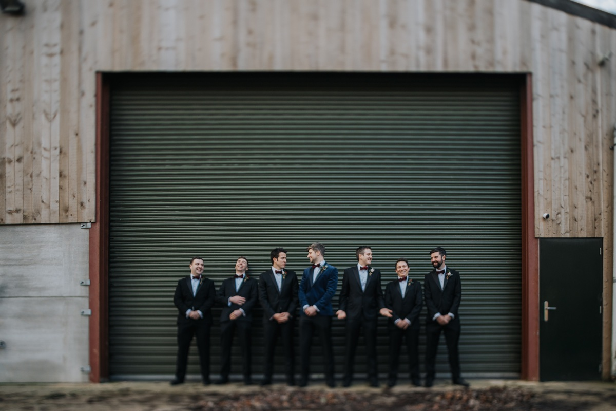 Tom and the guys hanging out by an old farm shed at The Normans. Photo by Bloom Weddings