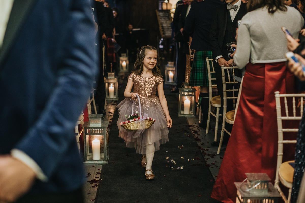 Sasha's flower girl leads the way down the aisle in The Normans Ceremony Barn. Photo by Bloom Weddings